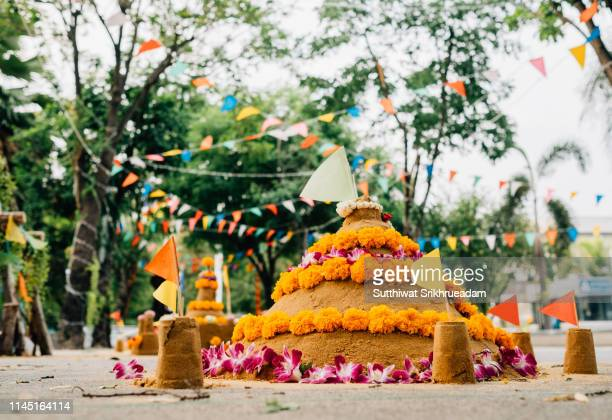close-up of sand pagoda against bunting and trees - buddhist new year stock pictures, royalty-free photos & images