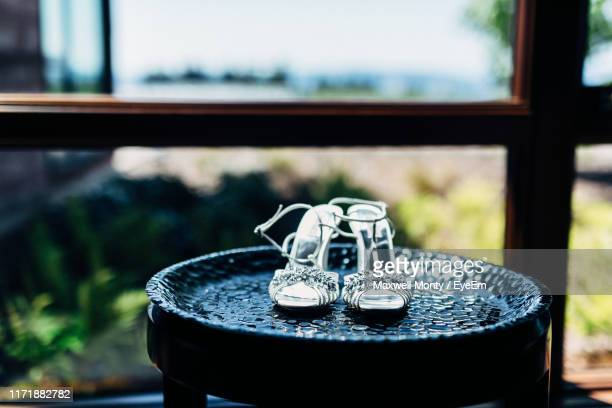 close-up of sandal on table against window - monty shadow stock photos and pictures