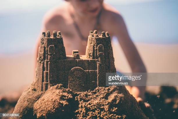 close-up of sandcastle built by boy on summer holidays - castle stock pictures, royalty-free photos & images