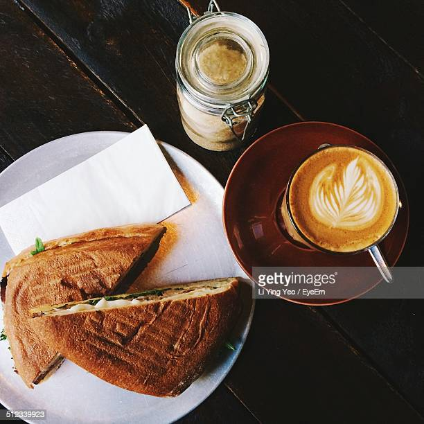 Close-up of sandwich and cappuccino served on table