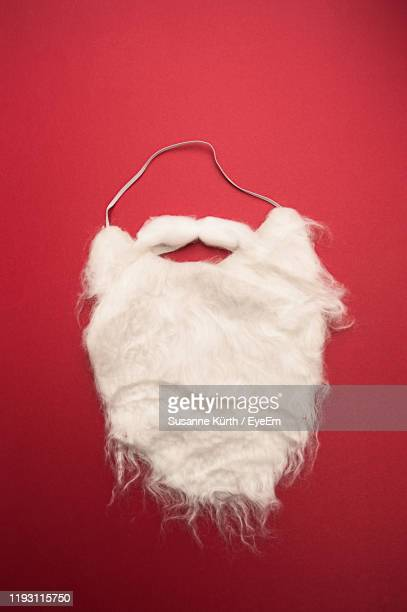 close-up of santa beard against red background - facial hair stock pictures, royalty-free photos & images