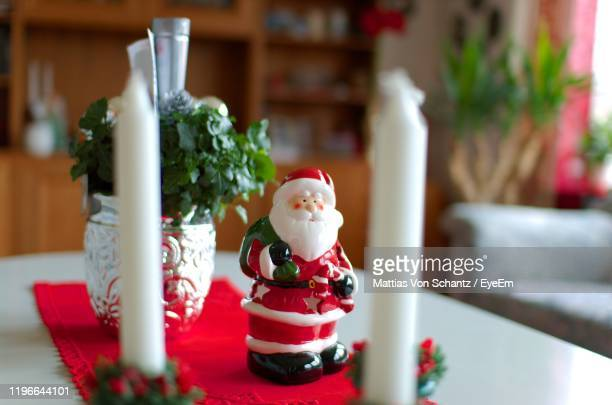 close-up of santa claus figurine on table - christmas decore candle stock pictures, royalty-free photos & images