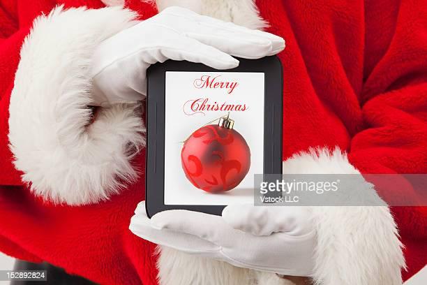 Close-up of Santa Claus holding digital tablet