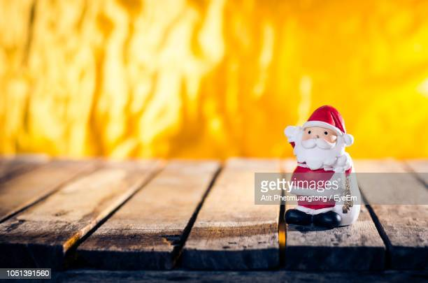 close-up of santa claus on wooden table against fire - santa close up stock pictures, royalty-free photos & images