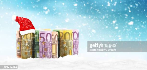 close-up of santa hat over paper currency on snow - christmas cash stock pictures, royalty-free photos & images