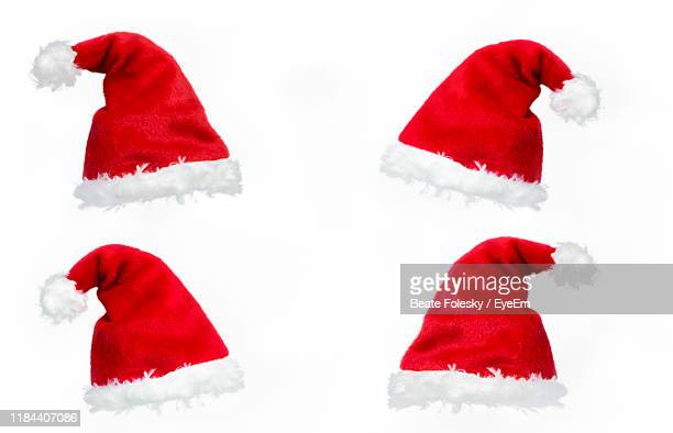close-up of santa hats over white background - hat stock pictures, royalty-free photos & images