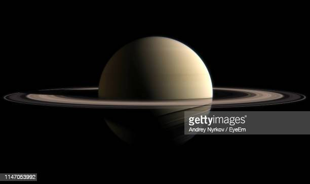 close-up of saturn against black background - saturn planet stock pictures, royalty-free photos & images