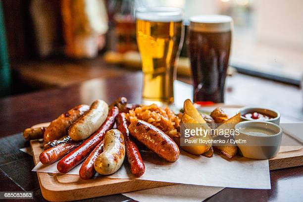 close-up of sausages and french fries served with beers on table - 盛り付け ストックフォトと画像