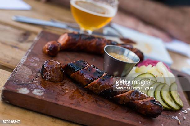 Close-Up Of Sausages And Salad On Cutting Board