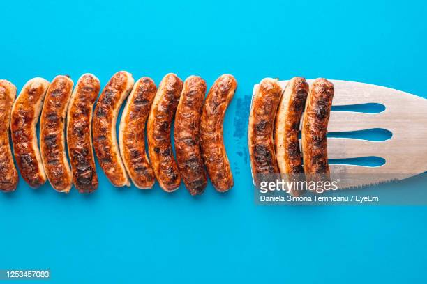 close-up of sausages on blue background - sausage stock pictures, royalty-free photos & images