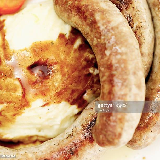 Close-up of sausages served with mash potatoes and gravy