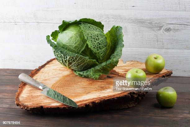 Close-Up Of Savoy Cabbage And Granny Smith Apples On Table
