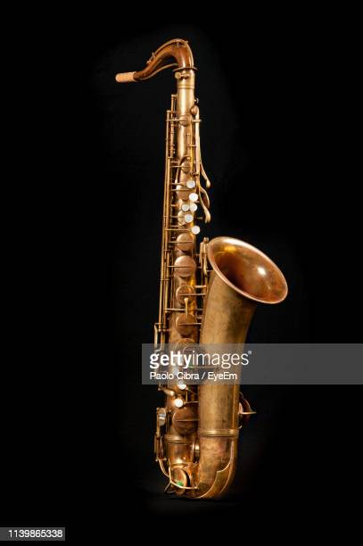close-up of saxophone against black background - saxophone stock pictures, royalty-free photos & images