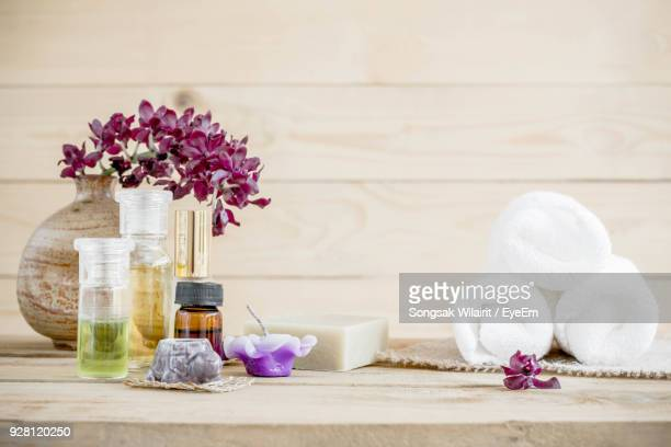 close-up of scented candles and oils on table - spa treatment stock pictures, royalty-free photos & images