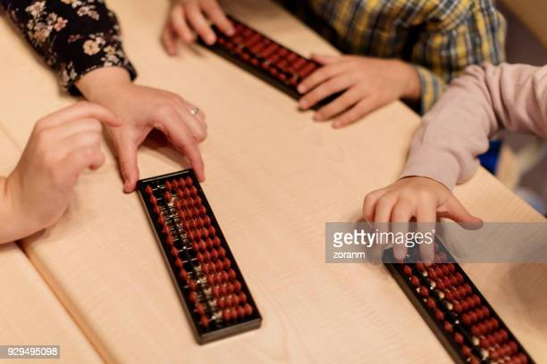 Close-up of school children using abacus
