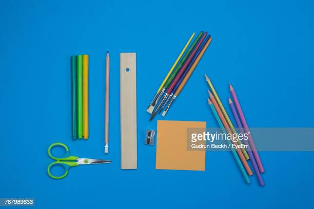 Close-Up Of School Supplies Over Blue Background