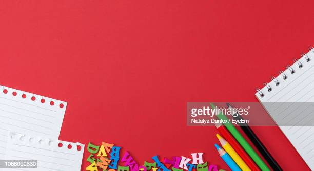 close-up of school supplies over red background - fournitures scolaires photos et images de collection