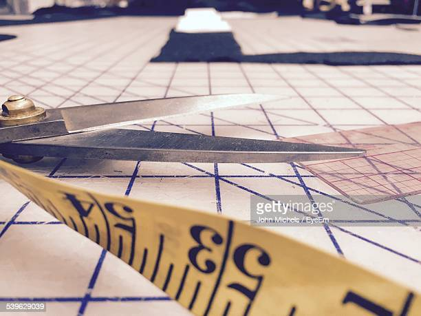 Close-Up Of Scissors And Tape Measure On Work Table In Workshop
