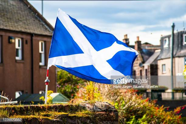 close-up of scotch flag against blue sky - scotland stock-fotos und bilder