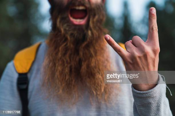 close-up of screaming man with beard making horn sign - opstand stockfoto's en -beelden