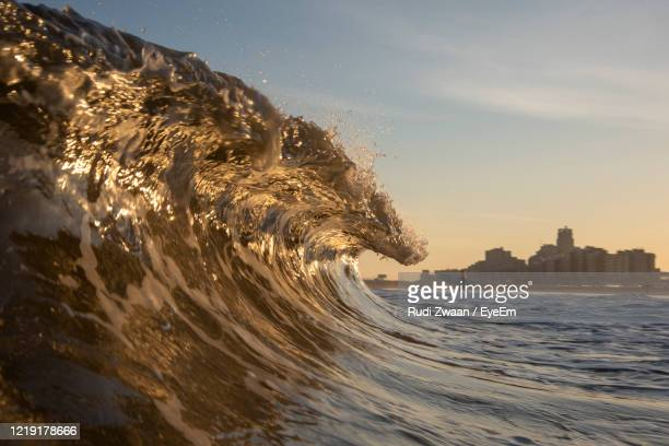 close-up of sea by city against sky during sunset - scheveningen stock pictures, royalty-free photos & images