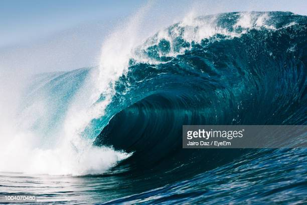 close-up of sea waves splashing against blue sky - onda imagens e fotografias de stock