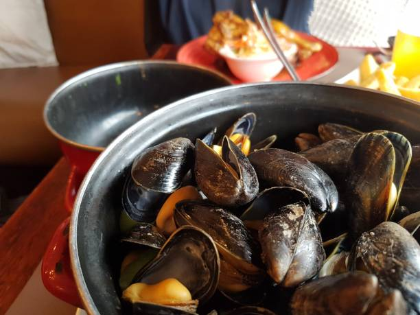 Close-Up Of Seafood Mussels  In Casserole As A Plate On Table