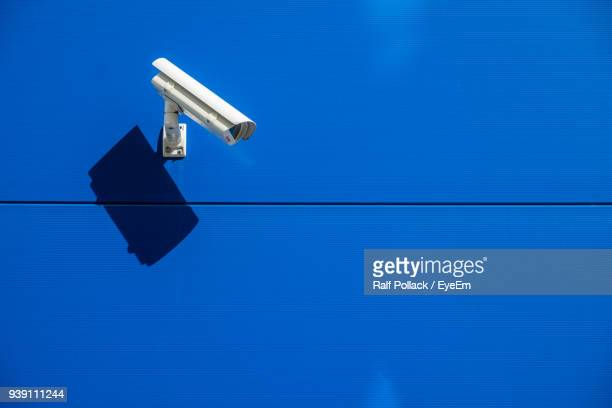 close-up of security camera mounted on blue wall - surveillance camera stock pictures, royalty-free photos & images