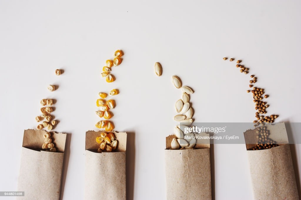 Close-Up Of Seeds Spilling From Paper Bag Against White Background : Stock Photo