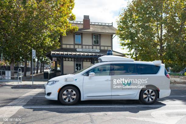 Closeup of self driving minivan with LIDAR and other sensor units and logo visible part of Google parent company Alphabet Inc driving past historic...