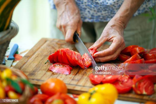 close-up of senior adult woman slicing tomatoes on cutting board - stock photo - chopping food stock pictures, royalty-free photos & images