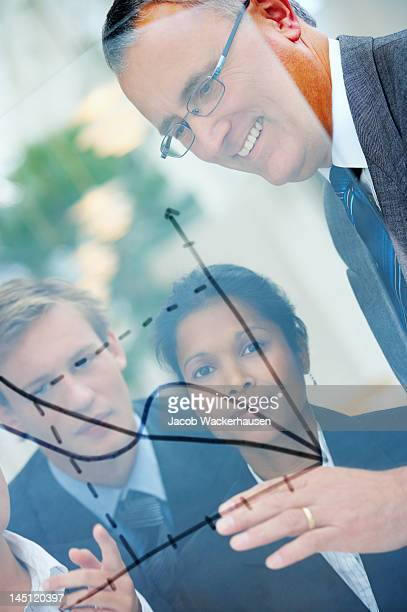 Close-up of senior businessman discussing future plans with his colleagues