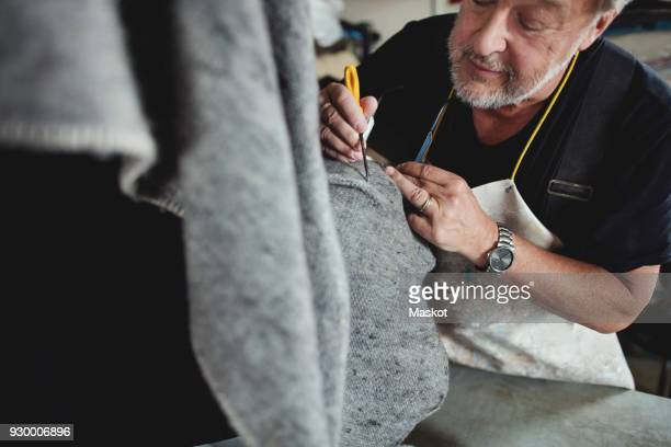 Close-up of senior craftsperson working on gray fabric at workshop
