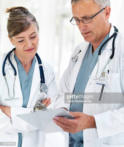 Close-up of senior doctors looking at reports