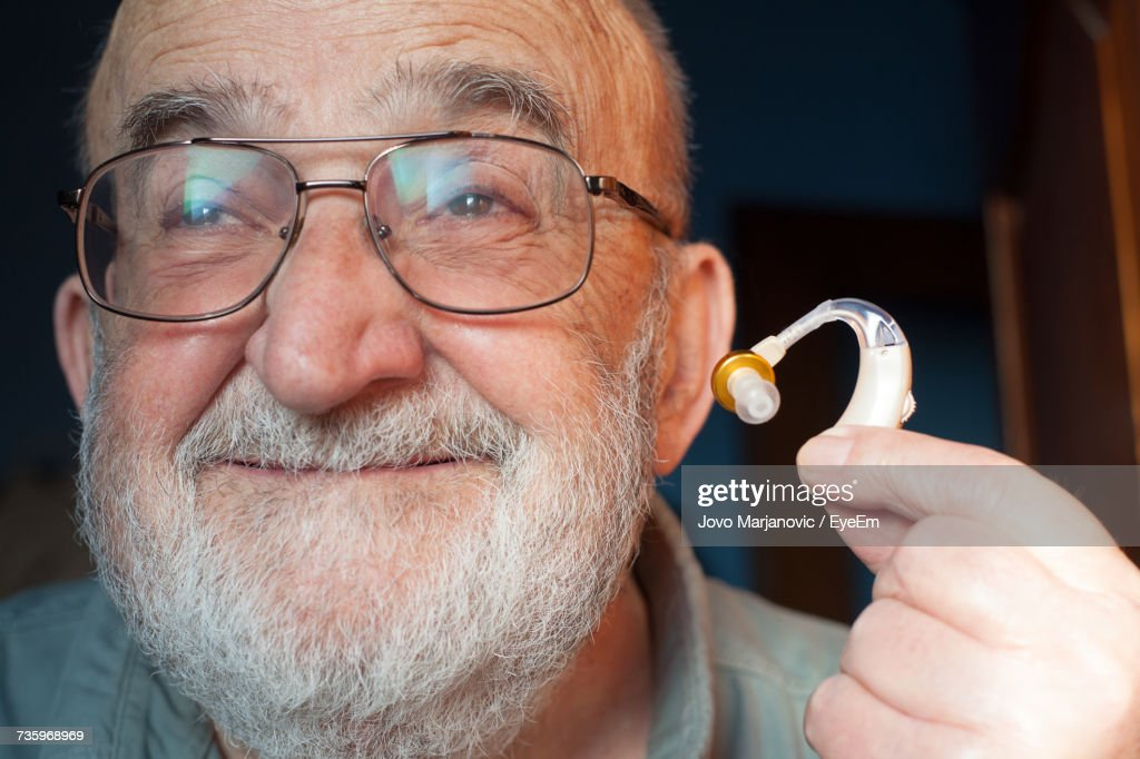 Close-Up Of Senior Man Holding Hearing Aid At Home : Stock Photo