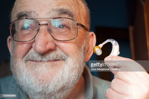 Close-Up Of Senior Man Holding Hearing Aid At Home