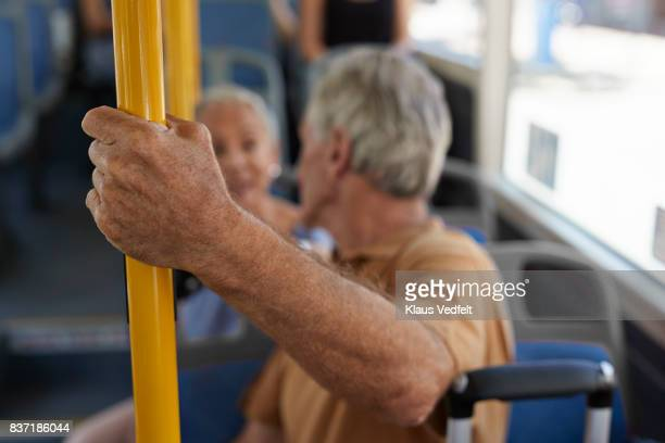 Close-up of senior man holding on to bar on public bus