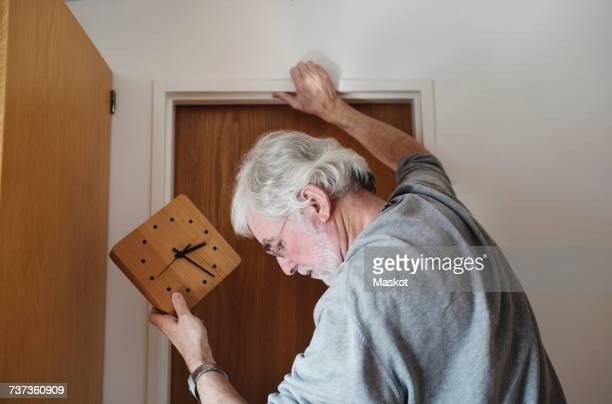 Close-up of senior man holding wall clock while standing by door on sunny day
