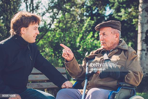 Close-Up of Senior Man in Wheelchair and Grandson Outdoors