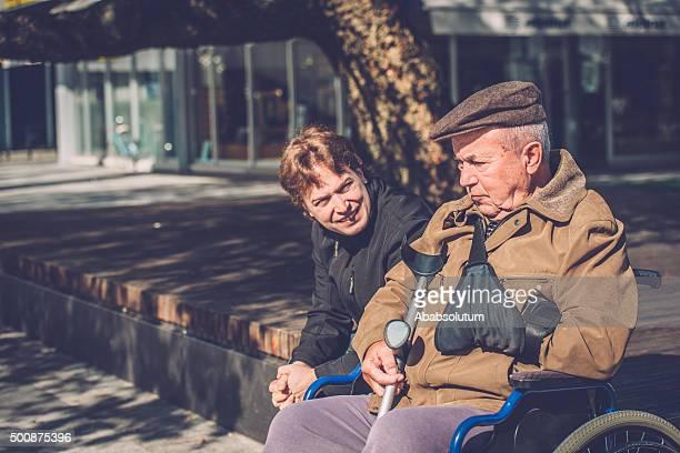 Close-Up de homem idoso em cadeira de rodas e neto ao ar livre