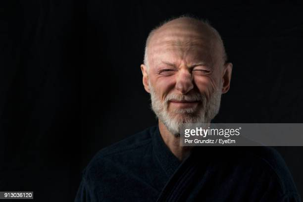 close-up of senior man making face against black background - squinting stock photos and pictures