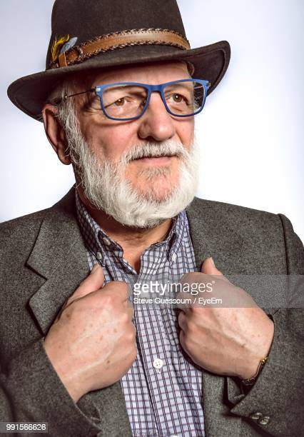 close-up of senior man wearing eyeglasses and coat against white background - steve guessoum stockfoto's en -beelden