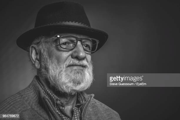close-up of senior man wearing hat against gray background - steve guessoum stockfoto's en -beelden