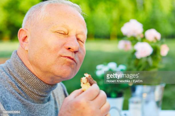 close-up of senior man with eyes closed eating sweet food at public park - 満たす ストックフォトと画像