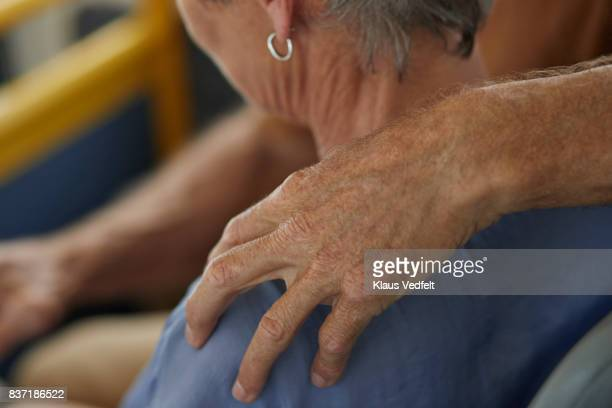 Close-up of senior man with hand on shoulder of his wife