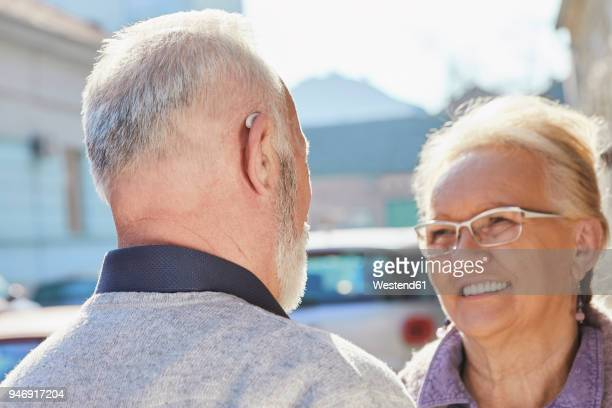 Close-up of senior man with hearing aid talking to senior woman