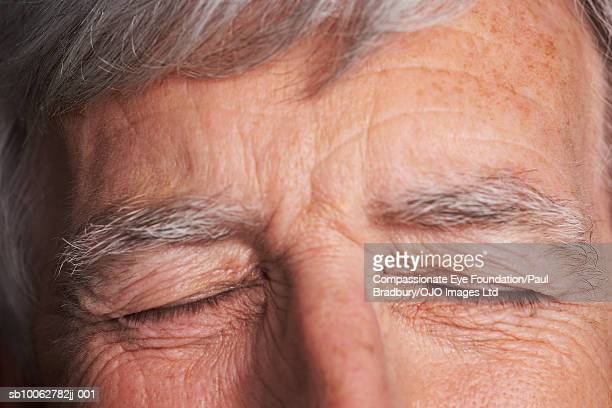 """close-up of senior man's closed eyes - """"compassionate eye"""" stock pictures, royalty-free photos & images"""