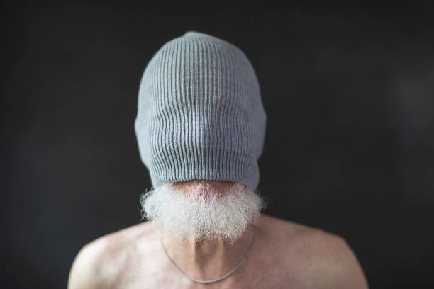 Close-up of senior man's face covered with knit hat against black background