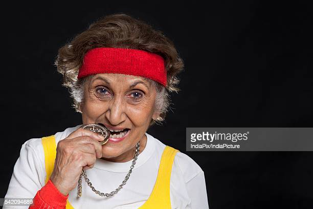 Close-up of senior woman biting locket