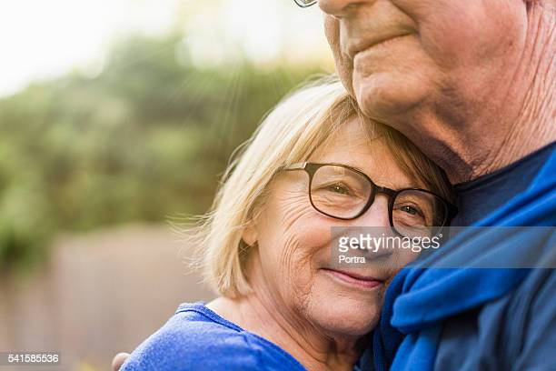 Close-up of senior woman embracing man
